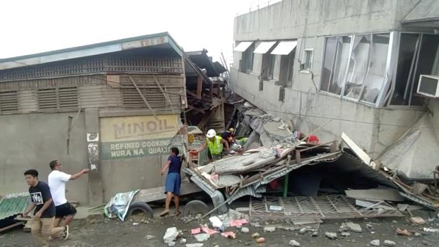 Rescue crew members look for trapped victims at collapsed building at Padada market, in Padada  Philippines December 15, 2019 in this still image obtained from social media video. VINCENT YAJ MAKIPUTIN/via REUTERS