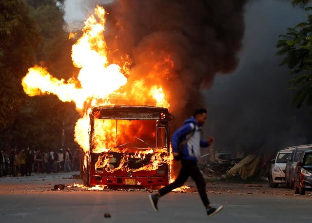A man runs past a burning bus that was set on fire by demonstrators during a protest against a new citizenship law, in New Delhi, India, December 15, 2019. REUTERS/Adnan Abidi