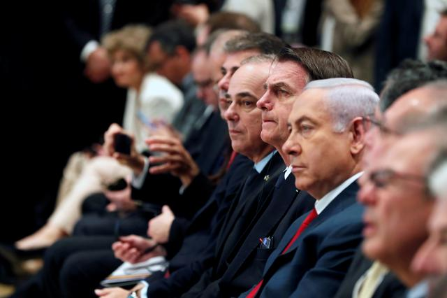 FILE PHOTO: Brazilian President Jair Bolsonaro sits next to Israeli Prime Minister Benjamin Netanyahu during an event with Israeli and Brazilian business people in Jerusalem April 2, 2019. REUTERS/Ronen Zvulun/File Photo
