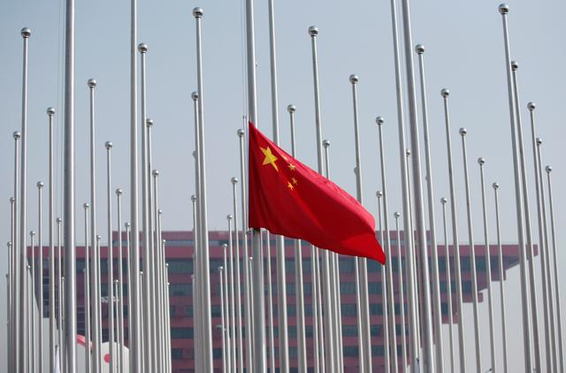FILE PHOTO: The Chinese flag is raised in front of the China Pavilion during a flag raising ceremony at the Shanghai World Expo site in Shanghai April 30, 2010. REUTERS/Alfred Jin/File Photo
