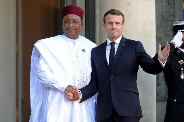FILE PHOTO: French President Emmanuel Macron weclomes Niger's President Mahamadou Issoufou as he arrives for a lunch at the Elysee Palace as part of the Paris Peace Summit in Paris, France, November 12, 2019. REUTERS/Johanna Geron