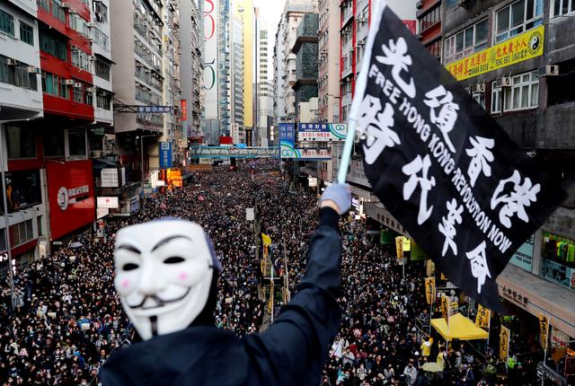FILE PHOTO: A protester wearing a Guy Fawkes mask waves a flag during a Human Rights Day march organised by the Civil Human Right Front in Hong Kong, December 8, 2019. REUTERS/Danish Siddiqui/File Photo