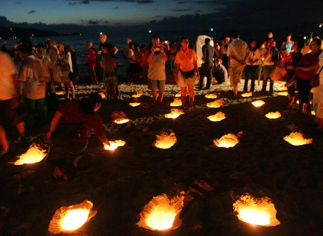 FILE PHOTO: Families of tsunami victims light candles during a vigil as part of a ceremony commemorating the first anniversary of the Indian Ocean tsunami on Patong beach in Phuket, Thailand December 26, 2005. REUTERS/Chaiwat Subprasom