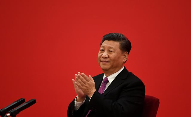 FILE PHOTO: China's President Xi Jinping applauds to Russian President Vladimir Putin as they talk via a video link, from the Great Hall of the People in Beijing, China December 2, 2019.  Noel Celis/Pool via REUTERS