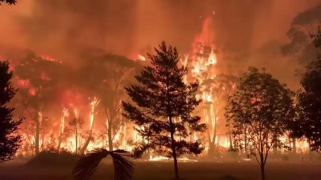 FILE PHOTO: A fire blazes across bush as seen from Mount Tomah in New South Wales, Australia December 15, 2019 in this still image obtained from social media video. NSW RFS – TERRY HILLS BRIGADE/via REUTERS
