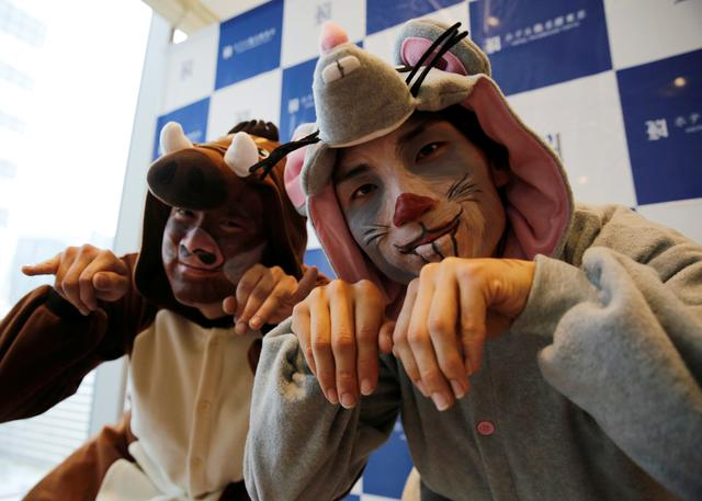 Window cleaners, dressed as a rat and a wild boar, this year and next year's Chinese zodiac animals, pose to photographers before cleaning the windows of Ryumeikan hotel during a promotional event to celebrate the upcoming new year in Tokyo, Japan, December 19, 2019. REUTERS/Kim Kyung-Hoon