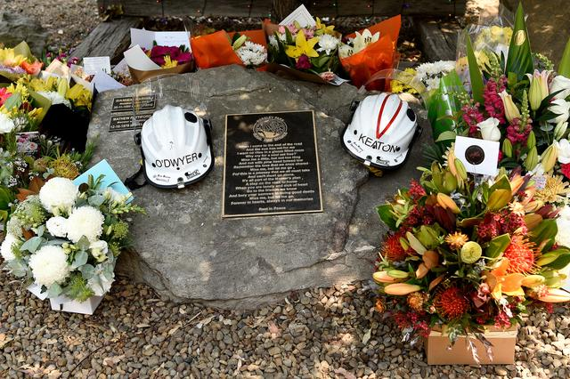 Flowers and the helmets of volunteer firefighters Andrew O'Dwyer and Geoffrey Keaton, who died when their fire truck was struck by a falling tree as it traveled through the front line of a fire, are seen at a memorial at the Horsley Park Rural Fire Brigade in Horsley Park, NSW, December 20, 2019. AAP Image/Bianca De Marchi/via REUTERS