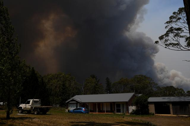 FILE PHOTO: A home is seen as smoke from the Grose Valley Fire rises in the distance, at Bilpin, New South Wales, Australia, December 21, 2019. AAP Image/Dan Himbrechts via REUTERS/File Photo