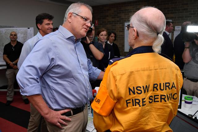 FILE PHOTO: Australia's Prime Minister Scott Morrison greets a volunteer during a visit to the Wollondilly Emergency Control Centre in Sydney, Australia, December 22, 2019. AAP Image/Joel Carrett/via REUTERS