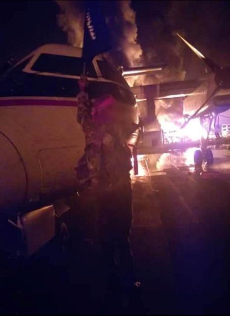 Una imagen distribuida por al Shabaab después del ataque a una base militar en Kenia muestra a un militante de Somalia al Shabaab sosteniendo la bandera del grupo junto a un avión en llamas, que se dice que está en el aeródromo de Manda Bay en Manda, Lamu, Kenia, el 5 de enero de 2020. Al-Shabaab / Folleto vía REUTERS