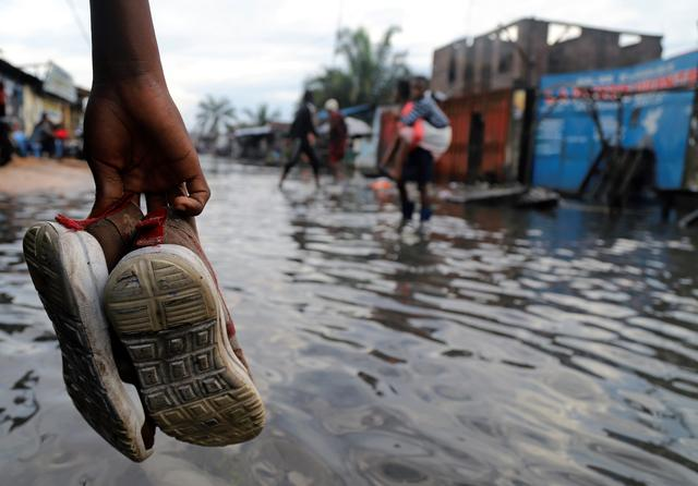 A Congolese man carries his shoes as he wades through floodwaters along a street after the Congo River burst its banks due to heavy rainfall in Kinshasa, Democratic Republic of Congo January 9, 2020. REUTERS/Kenny Katombe