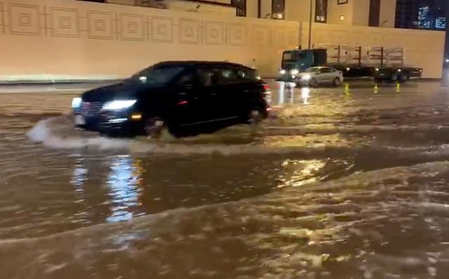 Cars drive through flooded streets in Dubai, United Arab Emirates, in the early hours of January 11, 2020 in this still image from social media video obtained by REUTERS