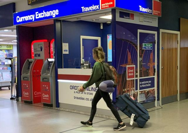 FILE PHOTO: A passenger walks past a Travelex currency exchange at Manchester Airport in Manchester, Britain January 8, 2020. REUTERS/Phil Noble/File Photo