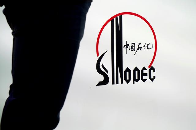 FILE PHOTO: A man stands next to a logo of Sinopec, or China Petroleum and Chemical Corporation, at an expo on rubber technology in Shanghai, China September 19, 2018. REUTERS/Stringer/File Photo