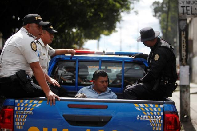A man detained by officers of the National Civil Police is pictured while sit on the bed of a police truck after Guatemalan President Alejandro Giammattei declared a state of alert in two municipalities plagued by gang violence, in Mixco, on the outskirts of Guatemala City, Guatemala January 17, 2020. REUTERS/Luis Vargas
