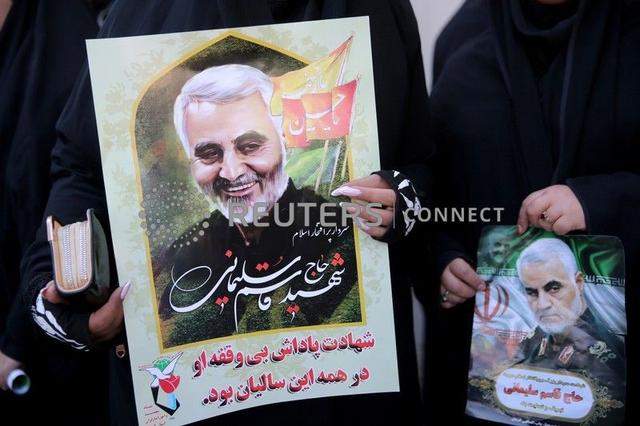 FILE PHOTO: Women hold pictures of Iranian Major-General Qassem Soleimani, head of the elite Quds Force, who was killed in an air strike at Baghdad airport, during a funeral procession and burial at his hometown in Kerman, Iran January 7, 2020. Mehdi Bolourian/Fars News Agency/WANA (West Asia News Agency) via REUTERS
