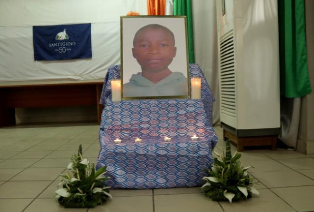 A poster of Barthelemy Laurent Guibahi Ani, a 14 years old boy who was found dead in the undercarriage of an Air France plane, is seen flanked by candles during a tribute prayer in Abidjan, Ivory Coast January 17, 2020. Picture taken January 17 2020. REUTERS/Luc Gnago