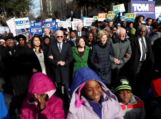Democratic U.S. 2020 presidential candidates including Rep. Tulsi Gabbard, former U.S. Vice President Joe Biden, Senator Amy Klobuchar, Senator Elizabeth Warren and Senator Bernie Sanders walk arm-in-arm with local African-American leaders during the Martin Luther King Jr. (MLK) Day Parade in Columbia, South Carolina, U.S., January 20, 2020.  REUTERS/Randall Hill