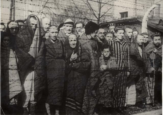 Holocaust survivors stand behind a barbed wire fence after the liberation of Nazi German death camp Auschwitz-Birkenau in 1945 in Nazi-occupied Poland, in this handout picture obtained by Reuters on January 19, 2020. Courtesy of Yad Vashem Archives/Handout via REUTERS