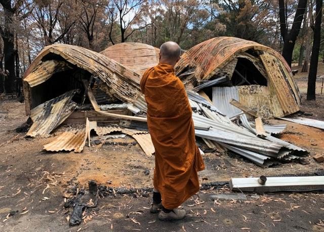 The Abbot of Sunnataram Forest Monastery, Phra Mana, 56, looks at the ruins of a burnt female dormitory in Bundanoon, Australia, January 21, 2020. REUTERS/Angie Teo