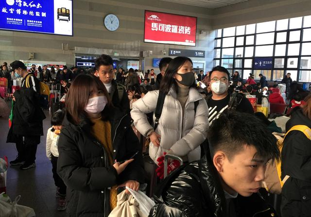 Passengers wearing masks wait to board trains at the Beijing West Railway Station, in Beijing, China January 20, 2020. REUTERS/Stringer