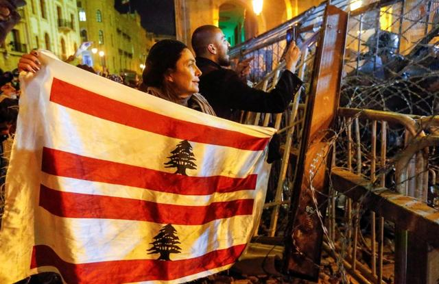 FILE PHOTO: A demonstrator holds the Lebanese flag during a protest against a ruling elite accused of steering Lebanon towards economic crisis in Beirut, Lebanon January 19, 2020. REUTERS/Mohamed Azakir/File Photo