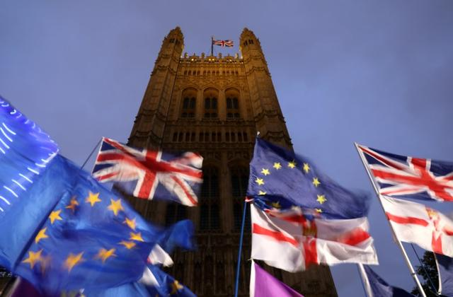 FILE PHOTO: Flags flutter outside the Houses of Parliament in London, Britain, October 21, 2019. REUTERS/Simon Dawson