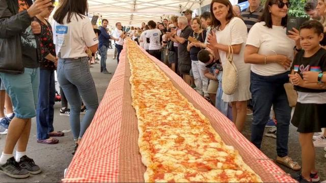 People look on as a 100m long margherita pizza sits on a table before receiving its final toppings, which was prepared by Pellegrini's Italian restaurant in their attempt to set a new record for Australia's longest pizza as part of a charity event to raise funds for the New South Wales Rural Fire Service, in Sydney, Australia, January 19, 2020, in this still image from video obtained via social media. Video taken January 19, 2020. INSTAGRAM/@ISSAC_EATSALOT via REUTERS