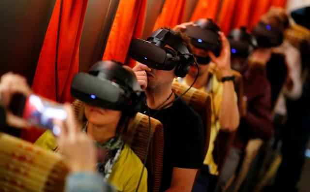 FILE PHOTO: People wear VR glasses at a new permanent Timeride exhibition about the divided city in Berlin, Germany, August 22, 2019. REUTERS/Hannibal Hanschke