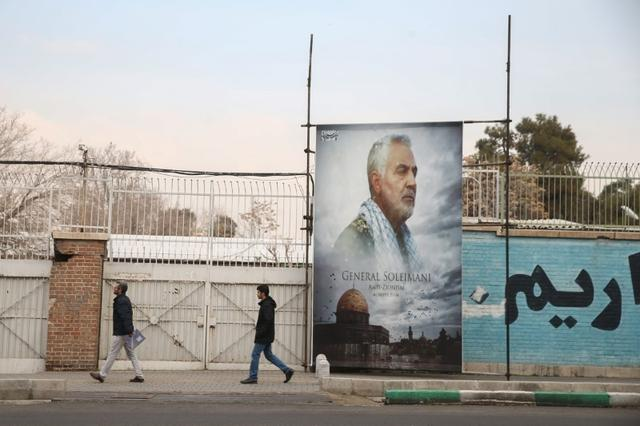 FILE PHOTO: People walk past a picture of Iranian Major-General Qassem Soleimani, head of the elite Quds Force, who was killed in an air strike at Baghdad airport, as it is seen in front of the former U.S. Embassy's building in Tehran, Iran, January 21, 2020. Nazanin Tabatabaee/WANA
