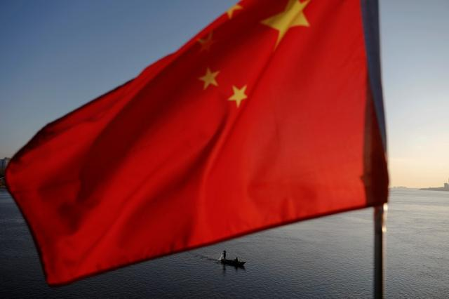 FILE PHOTO: North Korean fishermen are seen as a Chinese flag flutters from the Broken Bridge as the sun sets over the Yalu River between the North Korean town of Sinuiju and Dandong in Liaoning Province, China, November 19, 2017. REUTERS/Damir Sagolj/File Photo