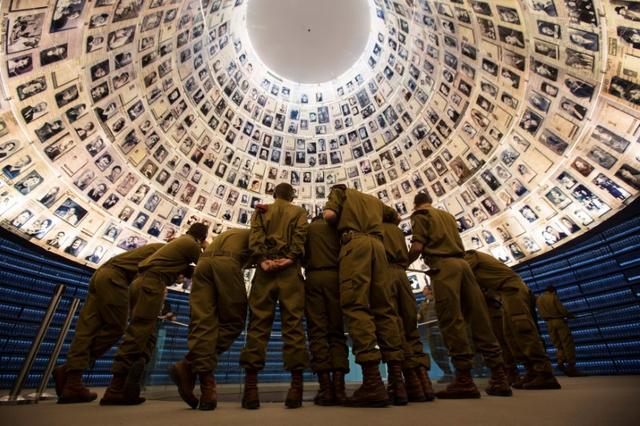 FILE PHOTO: Israeli soldiers stand under pictures of Jews killed in the Holocaust during a visit to the Hall of Names at the Yad Vashem Holocaust History Museum in Jerusalem January 26, 2014. Monday marks International Holocaust Remembrance Day to commemorate the victims of the Holocaust. REUTER/Baz Ratner/File Photo