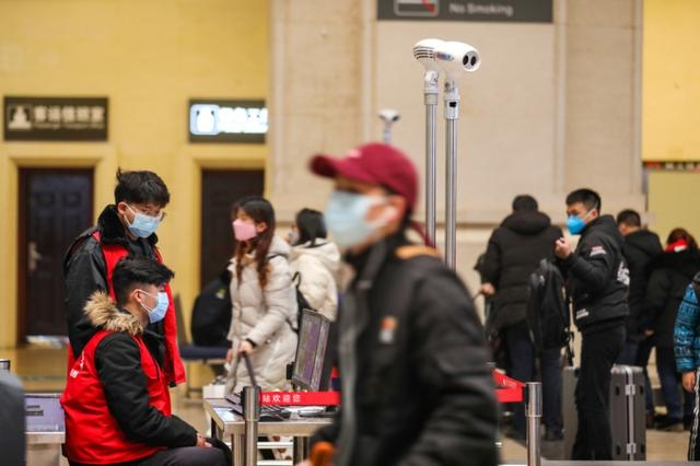 FILE PHOTO: Staff members wearing masks monitor thermal scanners that detect temperatures of passengers at the security check inside the Hankou Railway Station in Wuhan, Hubei province, China January 21, 2020. China Daily via REUTERS