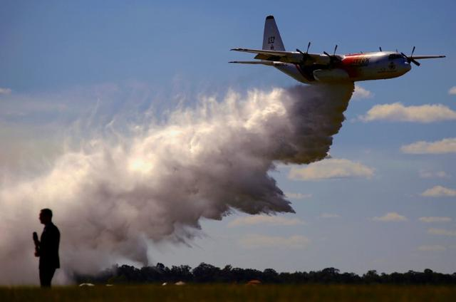 FILE PHOTO: A television reporter stands in front of a Large Air Tanker (LAT) C-130 Hercules as it drops a load of around 15,000 litres during a display by the Rural Fire Service ahead of the bushfire season at RAAF Base Richmond  Sydney, Australia, September 1, 2017.  REUTERS/David Gray/File Photo