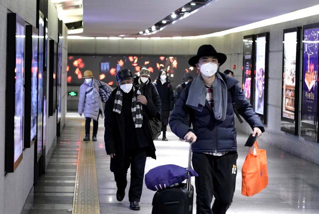 FILE PHOTO: People wearing masks walk through an underground passage to the subway in Beijing, China January 21, 2020. REUTERS/Jason Lee