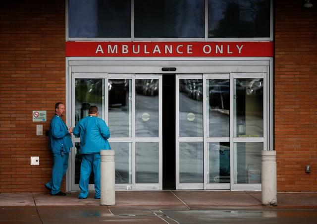 Employees in scrubs talk next to the ambulance entrance at Providence Regional Medical Center after a spokesman from the U.S. Centers for Disease Control and Prevention (CDC) said a traveler from China has been the first person in the United States to be diagnosed with the Wuhan coronavirus, in Everett, Washington, U.S. January 21, 2020.  REUTERS/Lindsey Wasson