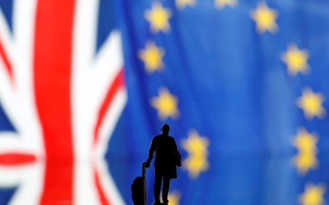 Small toy figure is seen in front of UK and European Union displayed flags in this illustration picture, October 17, 2019. REUTERS/Dado Ruvic/Illustration
