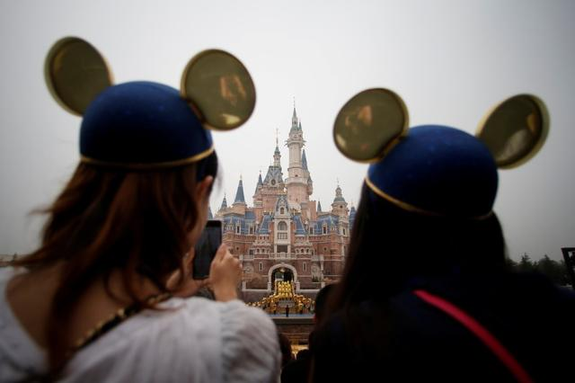 FILE PHOTO: Women wearing Mickey Mouse ears watch the opening ceremony at Shanghai Disney Resort in Shanghai, China, June 16, 2016. REUTERS/Aly Song/File Photo