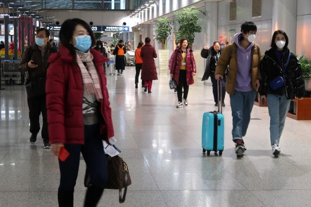 Passengers wearing masks are seen at the terminal hall of the Beijing Capital International Airport, in Beijing, China January 23, 2020. REUTERS/Martin Pollard