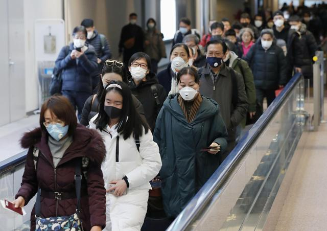 FILE PHOTO: Passengers arriving from the Chinese city of Wuhan arrive at Narita Airport in Chiba, Japan in this photo taken by Kyodo January 23, 2020. Mandatory credit Kyodo/via REUTERS