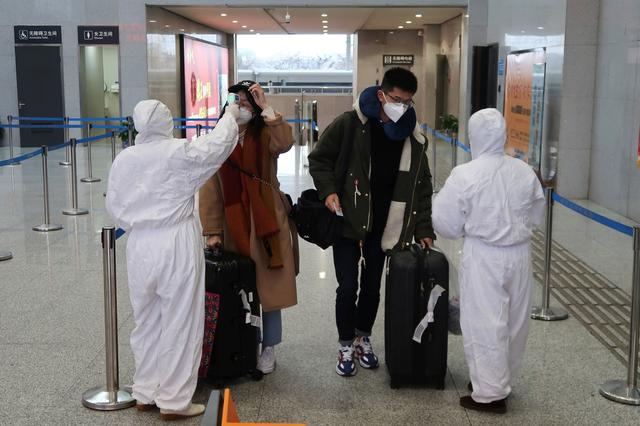 Workers in protective suits check the temperature of passengers arriving at the Xianning North Station on the eve of the Chinese Lunar New Year celebrations, in Xianning, a city bordering Wuhan to the north, in Hubei province, China January 24, 2020. REUTERS/Martin Pollard