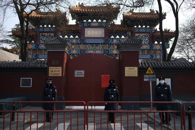Police officers stand guard in front of the closed gate of Lama Temple where a notice saying that the temple is closed for the safety concern following the outbreak of a new coronavirus is seen, in Beijing, China January 25, 2020. REUTERS/Carlos Garcia Rawlins