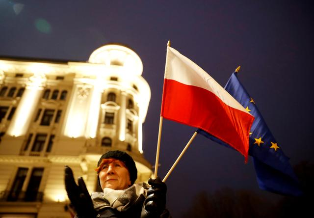 FILE PHOTO: A woman holds Polish an EU flags as she attends a protest against judiciary reform in Warsaw, Poland January 11, 2020. REUTERS/Kacper Pempel/File Photo