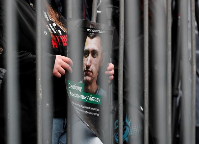 FILE PHOTO: A participant holds a placard while standing behind a metal barrier during a rally to demand the release of jailed protesters, who were detained during opposition demonstrations for fair elections, in Moscow, Russia September 29, 2019. The placard shows protester Konstantin Kotov, who was sentenced to four years in prison for participation in unauthorized rallies. REUTERS/Shamil Zhumatov