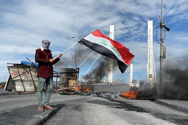 A demonstrator holds Iraqi flag near burning tires blocking a road, during ongoing anti-government protests in Nassiriya, Iraq January 25, 2020. REUTERS/Ahmed Dhahi