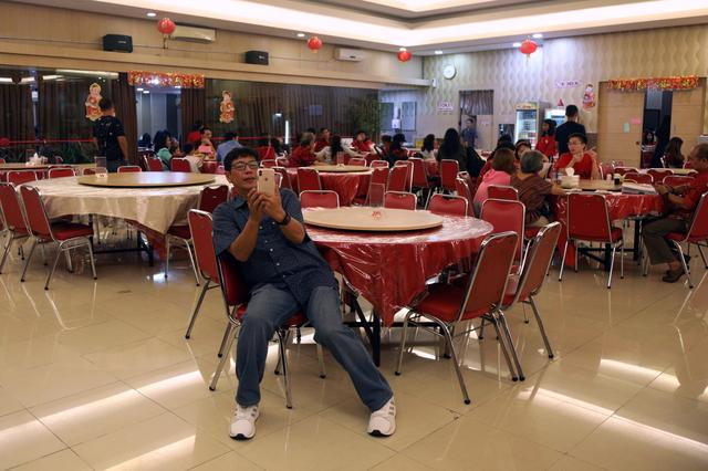Purnama, 49-year-old Ethnic-Chinese Indonesian, uses his smartphone as he attends Chinese Lunar New Year dinner and celebrations with other family members at a restaurant in Jakarta, Indonesia January 25, 2020. REUTERS/Irene Barlian