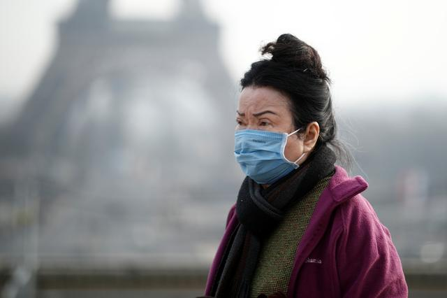 A woman wears a face mask on the Trocadero esplanade in front of the Eiffel Tower in Paris, France, January 25, 2020, as France confirmed three cases of the new coronavirus. REUTERS/Benoit Tessier