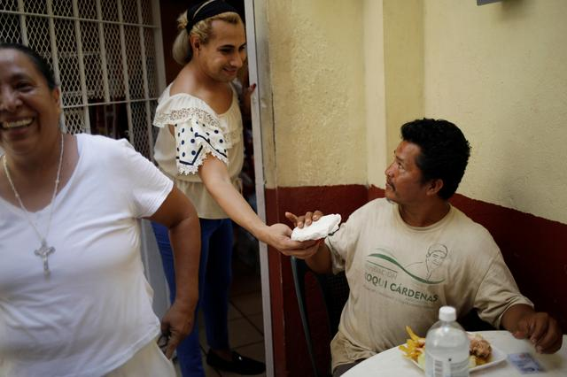 """Migrant Wilfredo Gomez, from Guatemala, receives food from another migrant at the """"Jesus el buen Pastor"""" shelter in Tapachula, Mexico, January 25, 2020. REUTERS/Andres Martinez Casares"""
