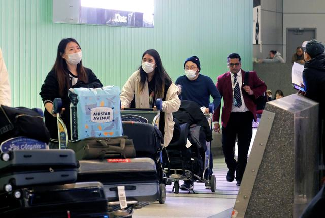 Passengers arrive at LAX from Shanghai, China, after a positive case of the coronavirus was announced in the Orange County suburb of Los Angeles, California, U.S., January 26, 2020.  REUTERS/Ringo Chiu