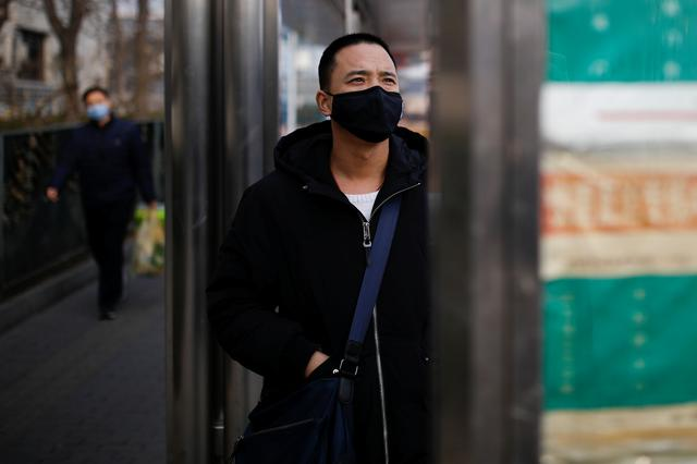 A man wearing a face mask looks at a board at a bus stop, as the country is hit by an outbreak of the new coronavirus, in Beijing, China January 27, 2020. REUTERS/Carlos Garcia Rawlins